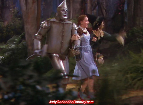 Judy Garland as Dorothy and her companions running through the forest