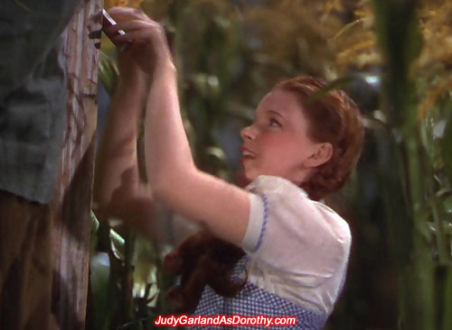Judy Garland as Dorothy bends the nail down on the pole