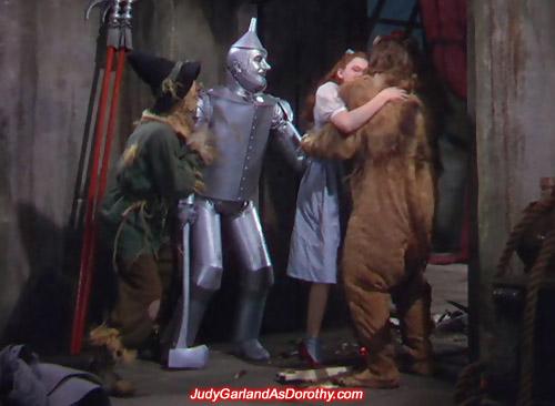 Judy Garland as Dorothy gives the Cowardly Lion a bear hug