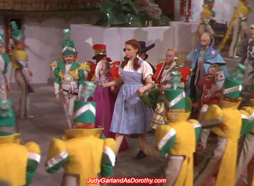 Judy Garland as Dorothy is escorted by the little people and their officials in Munchkinland