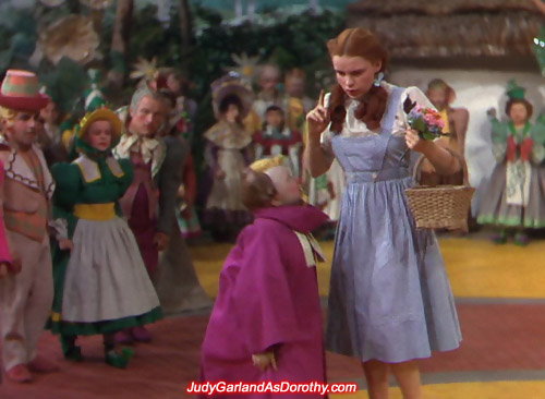 Judy Garland as Dorothy is guided by the Munchkins to the border of Munchkinland