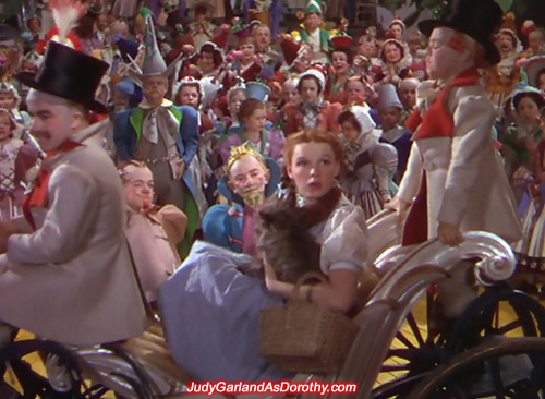 Judy Garland as Dorothy is transported in style around Munchkinland