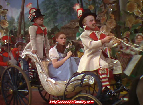 Judy Garland as Dorothy is treated like a princess on a horse-drawn carriage