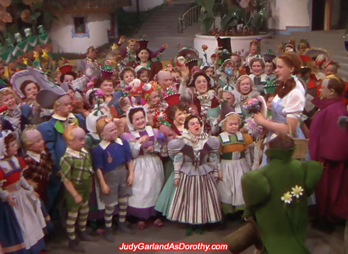 Judy Garland as Dorothy is welcomed by the Munchkins to their land in Oz