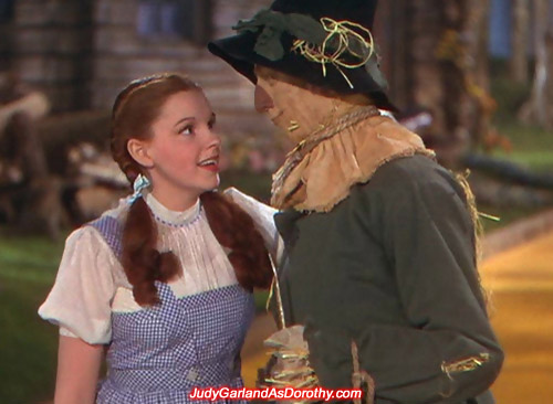 Judy Garland as Dorothy sees eye to eye with the Scarecrow