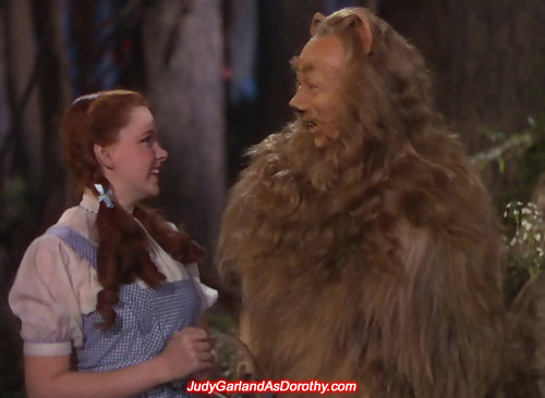 Judy Garland as Dorothy smiling at the Cowardly Lion