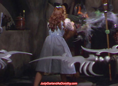 Judy Garland as Dorothy splashes water onto the Wicked Witch of the West