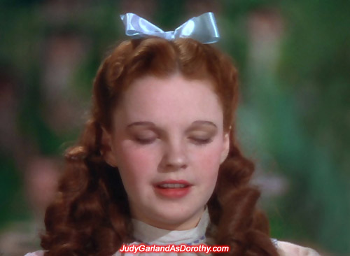 Judy Garland as Dorothy closes her eyes and thinking to herself 'There's no place like home'