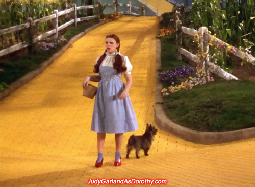 Teen powerhouse Judy Garland as Dorothy looking around on the Yellow Brick Road